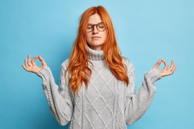 Mulher ruiva calma satisfeita segura a mão em gesto de ioga para equilíbrio mental fica com os olhos fechados medita para relaxar usa óculos e camisola.