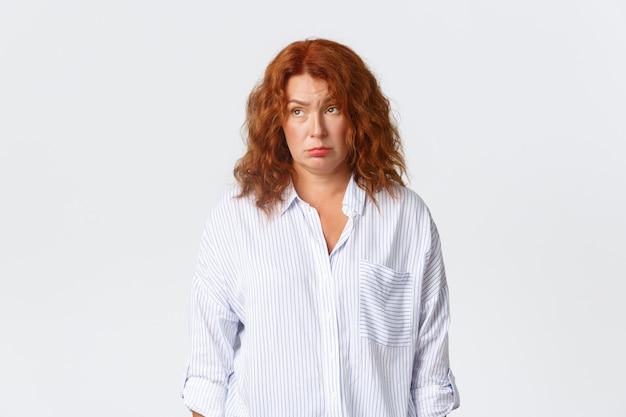 Mulher ruiva cansada relutante de camisa, desviando o olhar frustrado e exausto, sentindo-se indeciso em pé sobre um fundo branco chateado, tendo fadiga depois do trabalho, fundo branco.