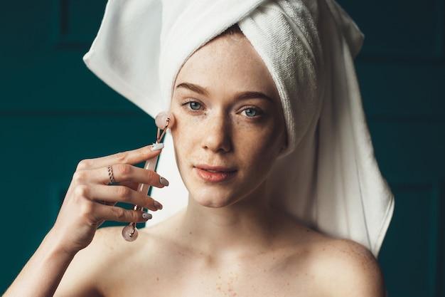Mulher ruiva caucasiana com sardas massageando o rosto com um rolo de pele olhando para a câmera com os ombros nus