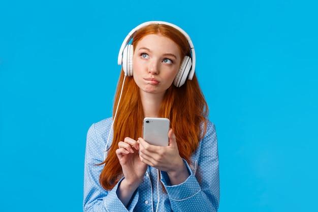 Mulher ruiva caucasiana pensativa e criativa, pensativa, garota sexy em roupas de dormir, olhando para cima pensando, usando fones de ouvido ouve música ou podcast, segurando o telefone, parede azul