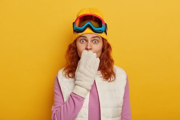 Mulher ruiva chocada cobre a boca e olha para a câmera, usa roupas e equipamentos especiais para esportes de inverno, gosta de esquiar ou praticar snowboard,