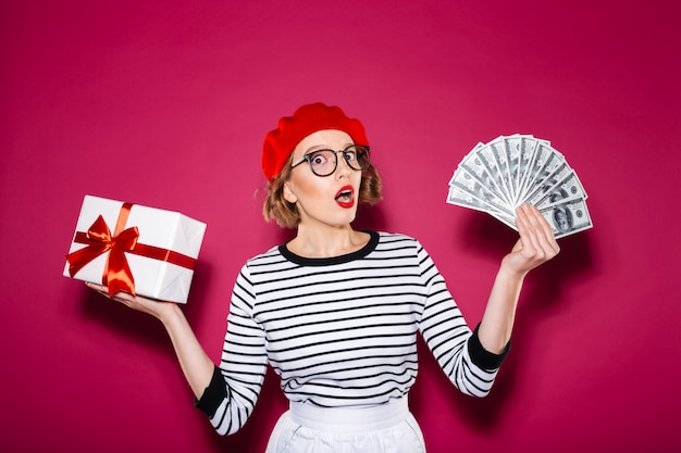 Mulher ruiva chocada em óculos, escolhendo entre dinheiro e caixa de presente enquanto olha para a câmera sobre rosa