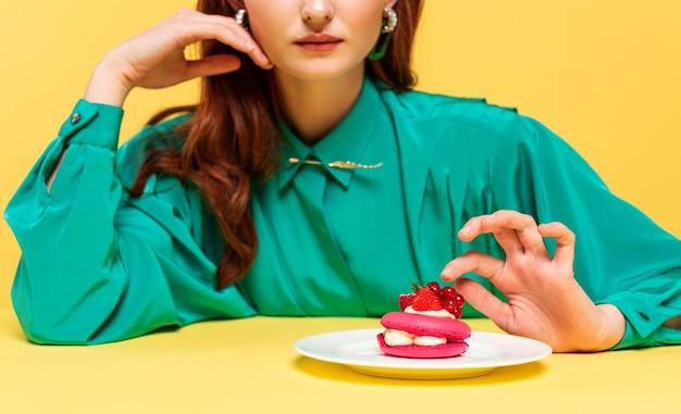 Mulher ruiva com blusa verde mostrando um bolo delicioso