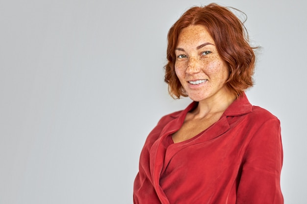 Mulher ruiva com blusa vermelha posando brilhando de felicidade, isolado no branco