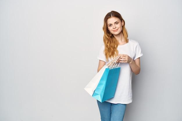 Mulher ruiva com camiseta branca e sacolas multicoloridas caminhando às compras
