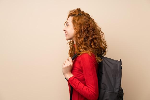 Mulher ruiva com camisola de gola alta com mochila