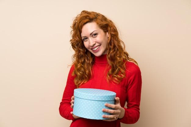Mulher ruiva com camisola de gola alta, segurando a caixa de presente