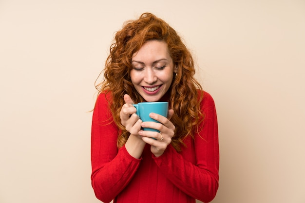 Mulher ruiva com camisola de gola alta, segurando a xícara de café quente