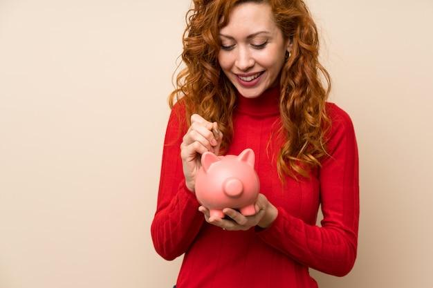 Mulher ruiva com camisola de gola alta, segurando um grande banco piggy
