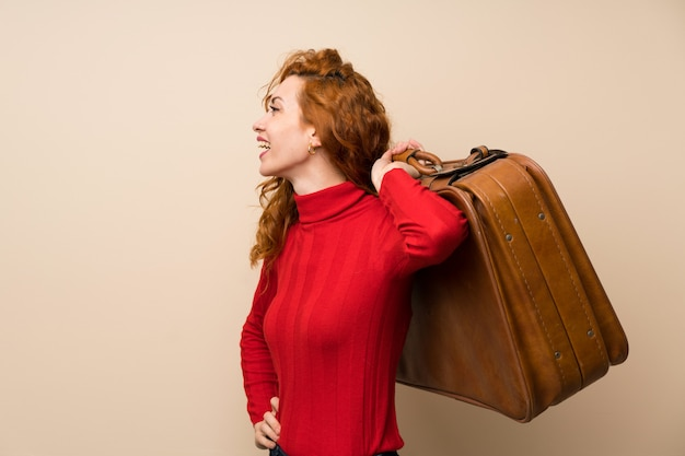 Mulher ruiva com camisola de gola alta segurando uma maleta vintage
