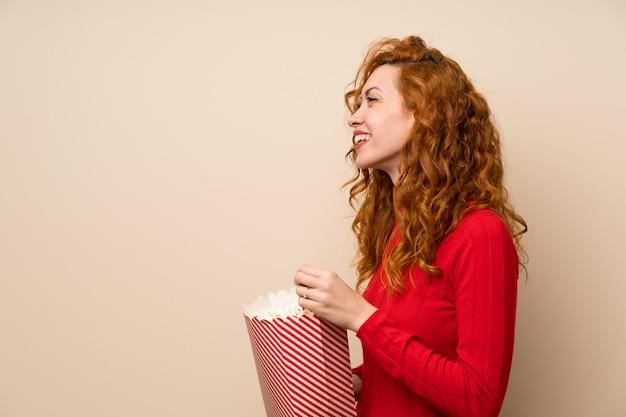Mulher ruiva com camisola de gola alta segurando uma tigela de pipocas