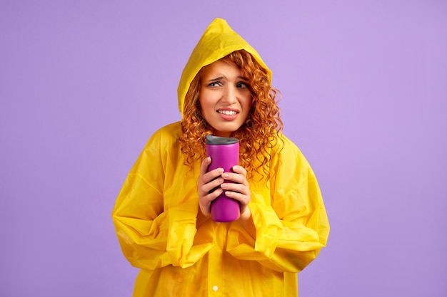 Mulher ruiva com capa de chuva amarela e caneca térmica isolada em roxo