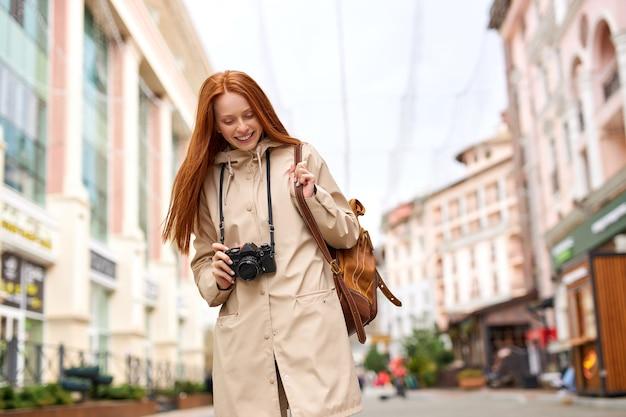 Mulher ruiva com casaco bege com mochila de couro marrom tirando fotos com a câmera de filme retrô no fundo do edifício histórico. conceito de cidade viajando sozinho. copie o espaço