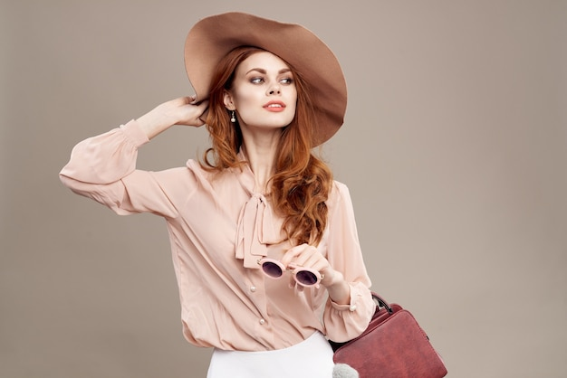Mulher ruiva com chapéu e camisa na maquiagem bege sorriso encanto jovem moda.