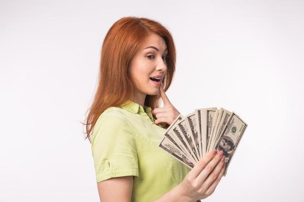 Mulher ruiva com dinheiro em fundo branco