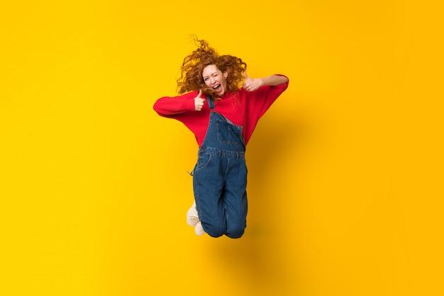 Mulher ruiva com macacão saltando sobre parede amarela isolada