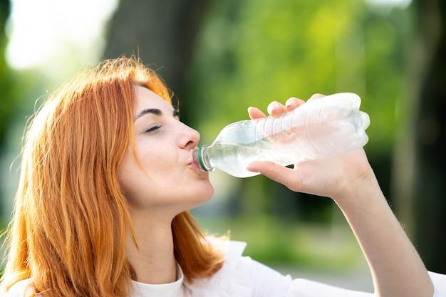 Mulher ruiva com sede jovem beber água de uma garrafa no parque de verão.