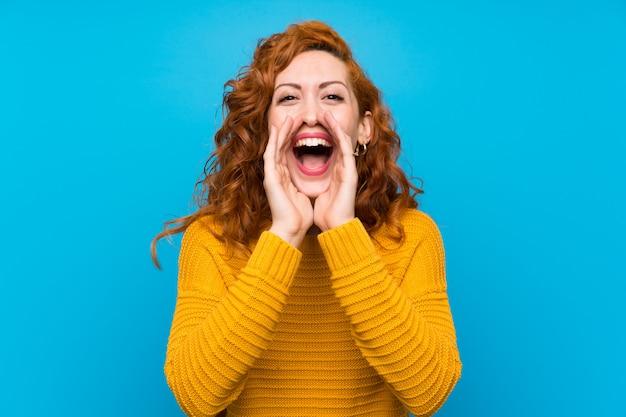 Mulher ruiva com suéter amarelo gritando e anunciando algo