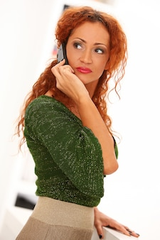 Mulher ruiva com telefone móvel