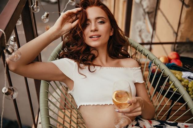 Mulher ruiva com top branco posando no terraço com uma taça de champanhe