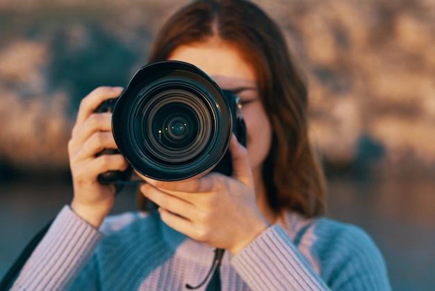 Mulher ruiva com uma câmera na natureza nas montanhas perto do rio Foto Premium