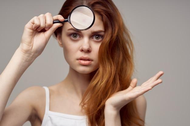 Mulher ruiva com uma camiseta branca com espinhas no rosto, close up