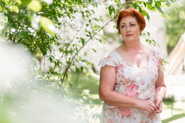 Mulher ruiva com vestido floral olhando para longe