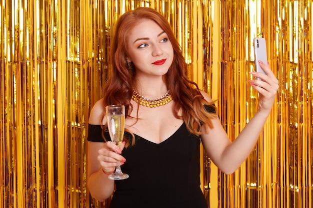 Mulher ruiva com vestido preto e colar tirando foto de selfie com seu telefone inteligente, segurando uma taça de vinho