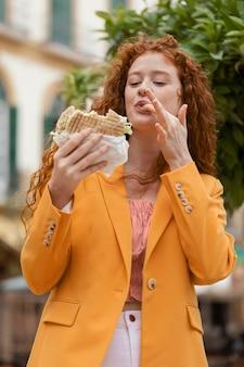 Mulher ruiva comendo comida de rua