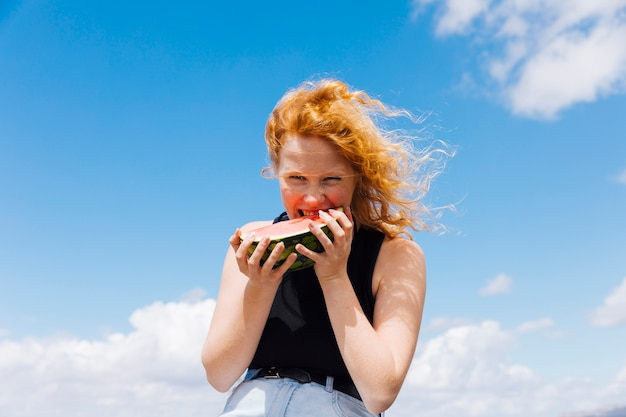 Mulher ruiva comendo fatia de melancia