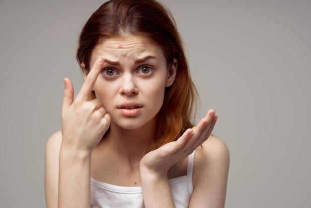 Mulher ruiva cosmetologia cuidados com a pele puberdade luz de fundo