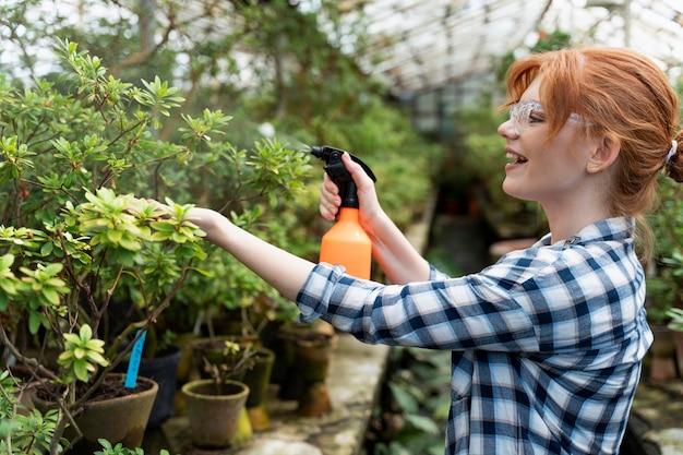 Mulher ruiva cuidando de suas plantas em uma estufa