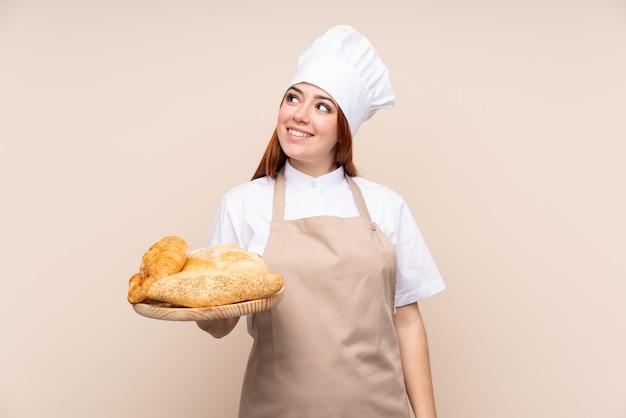 Mulher ruiva de adolescente em uniforme de chef. padeiro feminino segurando uma mesa com vários pães, olhando para cima enquanto sorrindo