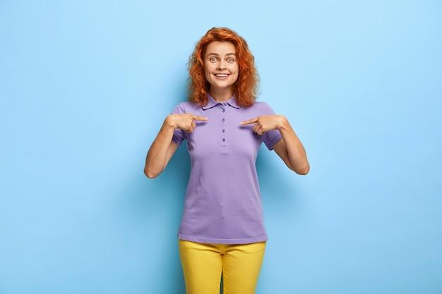Mulher ruiva de aparência agradável e encantada aponta para o espaço em branco da camiseta