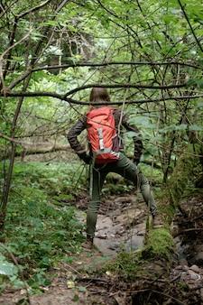 Mulher ruiva de cabelos longos viaja na floresta nublada de verão