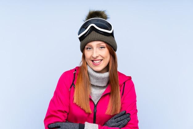 Mulher ruiva de esquiador com óculos de snowboard rindo