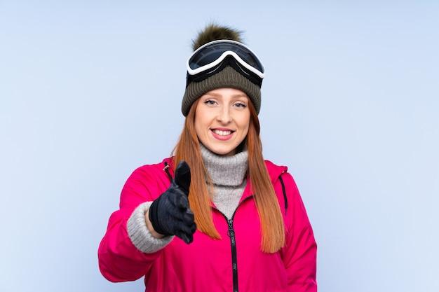 Mulher ruiva de esquiador com óculos de snowboard sobre aperto de mão isolado parede azul depois de um bom negócio