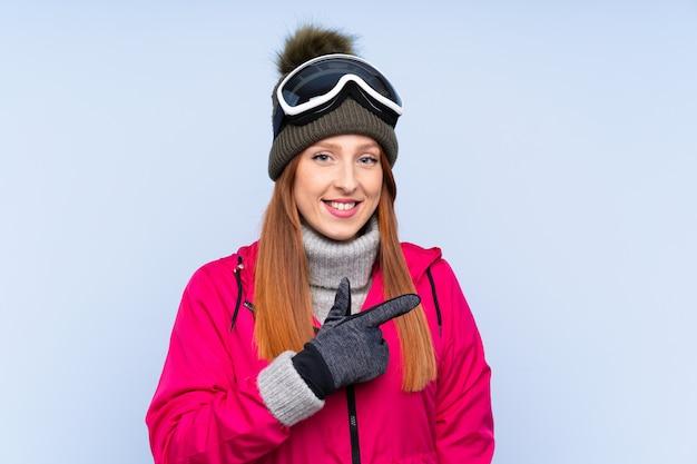 Mulher ruiva de esquiador com óculos de snowboard sobre parede azul isolada, apontando o dedo para o lado