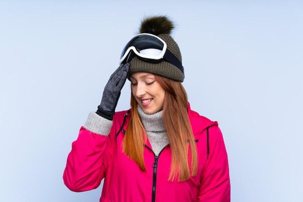 Mulher ruiva de esquiador com óculos de snowboard sobre parede azul isolada rindo