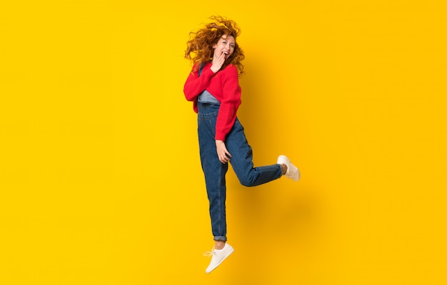 Mulher ruiva de macacão pulando parede amarela isolada