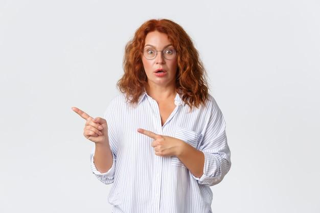 Mulher ruiva de meia-idade confusa e chocada de óculos reagir a algo estranho, ofegando e parecendo preocupada enquanto aponta para o canto superior esquerdo, em pé na parede branca.