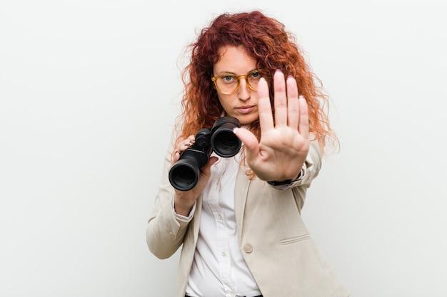 Mulher ruiva de negócios caucasiano jovem segurando um binóculo em pé com a mão estendida, mostrando o sinal de stop, impedindo-o.