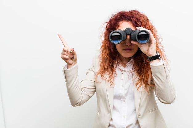 Mulher ruiva de negócios caucasiano jovem segurando um binóculo sorrindo alegremente apontando com o dedo indicador.