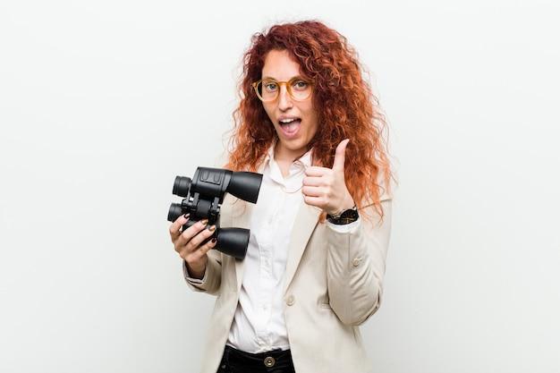 Mulher ruiva de negócios caucasiano jovem segurando um binóculo sorrindo e levantando o polegar