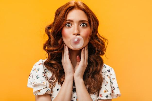 Mulher ruiva de olhos verdes de espanto olha para a câmera em fundo laranja. mulher de camiseta branca faz bolha de chiclete.