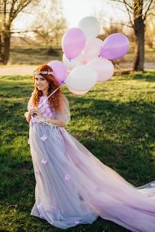 Mulher ruiva de vestido roxo andando no parque com balões na mão, ao pôr do sol