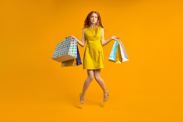 Mulher ruiva decepcionada com vestido segura pacotes de compras, chateada com as compras. linda mulher parece infeliz, não gosta de compra. mulher entediada e cansada compra presentes, isolados no amarelo, pulando