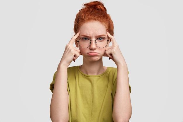 Mulher ruiva decepcionada mantém os dedos da frente nas têmporas, tem o rosto taciturno, franze o lábio inferior, pensa em algo vestido casualmente