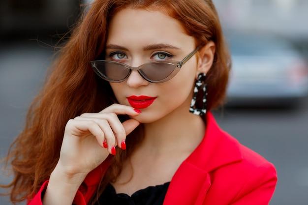 Mulher ruiva deslumbrante, olhando para a frente, segurando óculos. vestida com jaqueta vermelha casual.