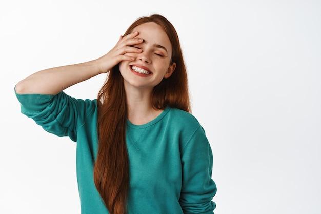 Mulher ruiva despreocupada rindo, sorrindo com dentes brancos, fecha os olhos e toca o rosto suavemente, sentindo-se livre e feliz, pisando em branco